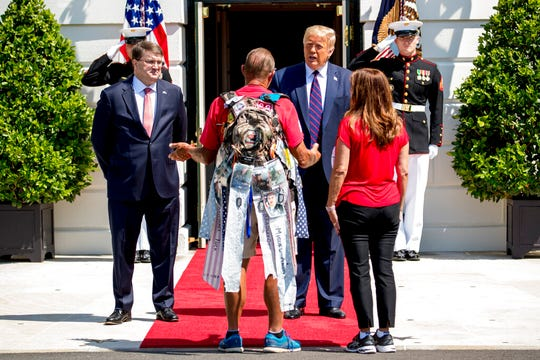 """President Donald Trump, accompanied by Veterans Affairs Secretary Robert Wilkie, left, and Karen Pence, the wife of Vice President Mike Pence, right, greets Terry Sharpe, center, known as the """"Walking Marine"""" at the White House in Washington, Monday, July 27, 2020. Sharpe has walked from Summerfield, N.C., to Washington to raise awareness of the current veteran suicide rate."""
