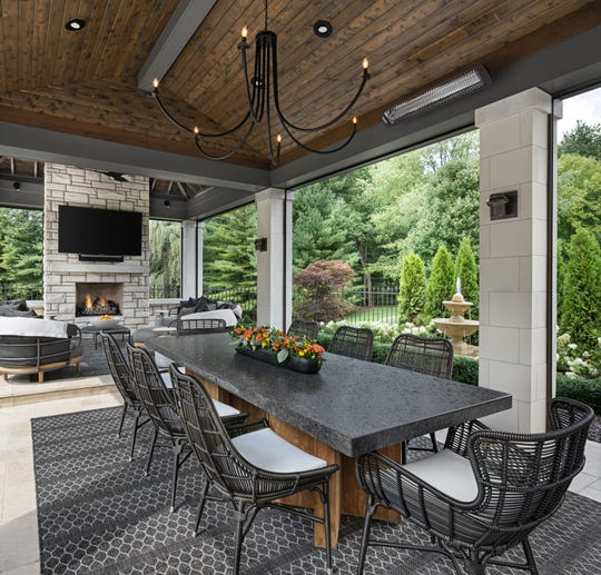 This Oakland Township outdoor room features a dining area, sitting area and large screen TV. Interior designer Marianne Jones worked with architect Glenda Meads on the space.