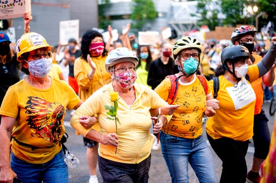 "Norma Lewis holds a flower while forming a ""wall of moms"" during a Black Lives Matter protest on Monday, July 20, 2020, in Portland, Ore."