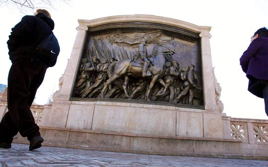 In this March 26, 2011, file photo, people walk past the memorial to Union Col. Robert Gould Shaw and the 54th Massachusetts Volunteer Infantry Regiment, near the Statehouse in Boston.
