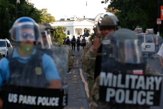 In this Monday, June 1, 2020, file photo police clear the area around Lafayette Park and the White House in Washington, as demonstrators gather to protest the death of George Floyd.
