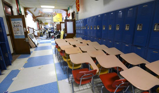 Students desks and other materials are stacked up in the Dickinson West Elementary School hallway as crews prepare classrooms for this year's social distancing requirements.