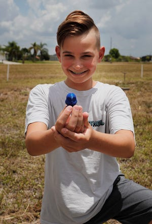 Alex Brown, 13, displays one of his burrowing owls, near his home in Cape Coral. He began making the petite figures of burrowing owls in order to raise money for their protection.