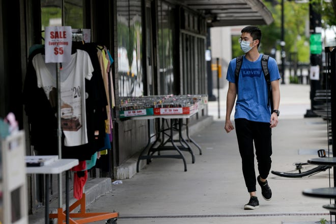 A man wears a mask as he walks along State Street, Monday, July 27, 2020 in West Lafayette.