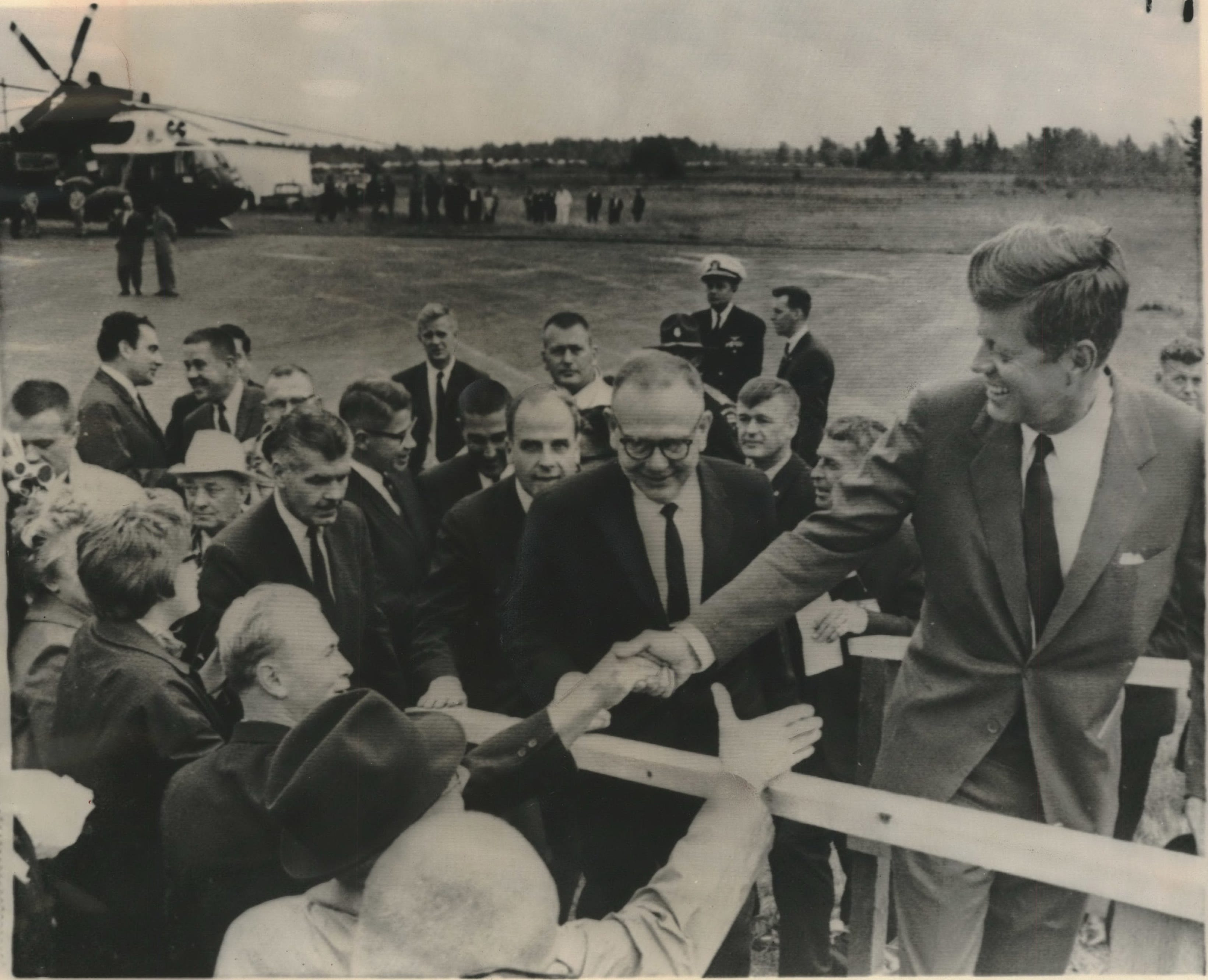 President John F. Kennedy shook hands with people in the crowd on Sept. 24, 1963 as he mounted the stairs to the speakers' platform at the Ashland airport after a helicopter tour over the Apostle Islands. Following him were Governor Reynolds, Senator Nelson, Interior Secretary Udall and Agriculture Secretary Freeman. The president spoke briefly before going back to Duluth, Minn.