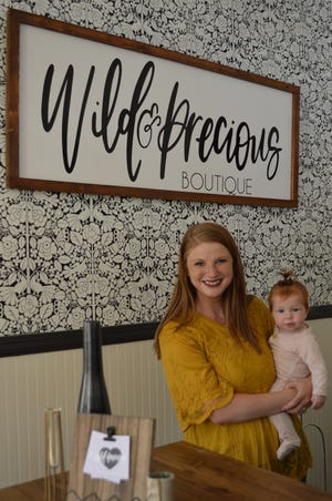Opal Stone owns Wild & Precious Clothing and Design Boutique in Grafton. Stone is holding her daughter, Lennon, at the new store at 1323 Wisconsin Ave.