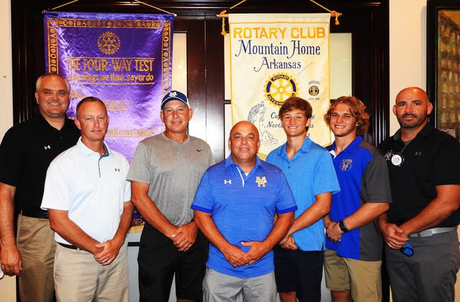 """On July 23, Rotarian of the Day Mike Stockton introduced his guests from the MHHS football team. New Head Coach Steve Ary talked about his plans for the future of Bomber Football and told Rotarians that he wanted to build not only a team that will win ballgames, but also a """"football community"""" that supported their team's success. Ary also talked about his coaching staff: Darren Acklin, Fred Crow, and Ryan Mallett. Assistant coach Acklin talked about his ties to this area and how excited he was to be here and work with these outstanding young men. Both coaches thanked Rotarian and MHPS Superintendent Jake Long for the great staff they put together this season, then congratulated MHHS Athletic Director Mitch Huskey for being selected as the """"Arkansas Athletic Director of the Year."""" Two of the team's senior players, tailback Gage Hershberger and cornerback Lawson Stockton, spoke to the club about the differences they are already seeing in the team under the new coaching staff. Coach Ary complimented both players for providing team leadership, setting a good work ethic, and displaying strong character on and off the field. Guests for the day included Matt and Nicole Hershberger, Gage's parents, plus James Boyett's wife Staci, and Sally Gilbert's co-worker Jacob Bruggemen. Pictured are (left to right) Rotarian of the Day Mike Stockton, MHHS Athletic Director Mitch Huskey, assistant football coach Darren Acklin, MHHS head football coach Steve Ary, cornerback Lawson Stockton, tailback Gage Hershberger and MHPS Superintendent/Rotarian Dr. Jake Long."""