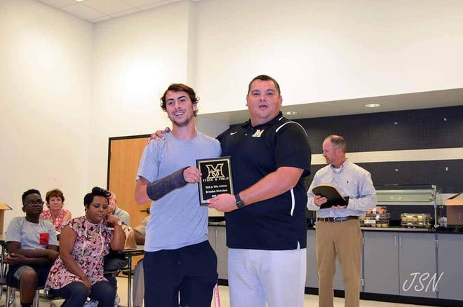 Milton track and field coach Joe Austin (right) is pictured during an undated awards ceremony at Milton High School. Austin passed away in July 2020 after a battle with COVID-19.