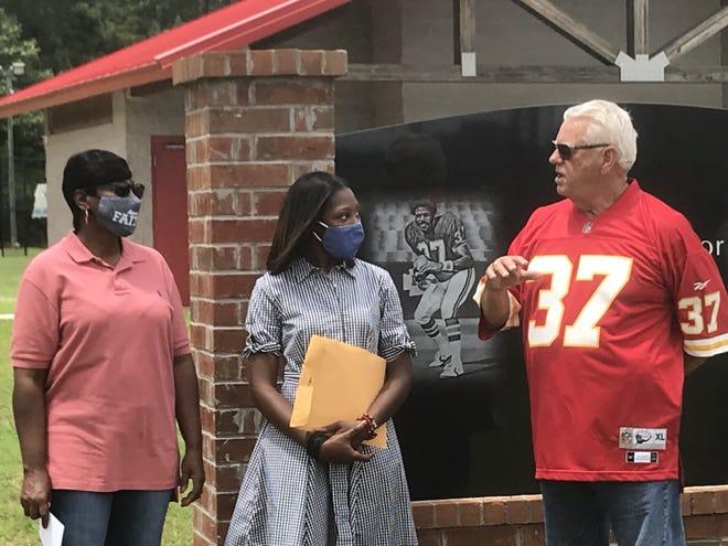 Marvin Dearman talks with Joe Delaney's widow, Carolyn Delaney, and youngest daughter, JoAnna Delaney, at Haughton's Joe Delaney Park Monday in Haughton.