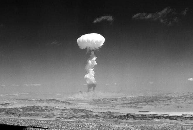 FILE - In this April 22, 1952 file photo a gigantic pillar of smoke with the familiar mushroom top climbs above Yucca Flat, Nev. during nuclear test detonation. A defense spending bill pending in Congress includes an apology to New Mexico, Nevada, Utah and other states affected by nuclear testing over the decades, but communities downwind from the first atomic test in 1945 are still holding out for compensation amid rumblings about the potential for the U.S. to resume nuclear testing. (AP Photo,File)