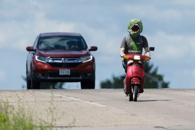 Kyle Connell rides his moped to the gym on Monday, July 27, 2020, along County Highway HH in Plover, Wis. Connell wears a dinosaur costume head on his commute.