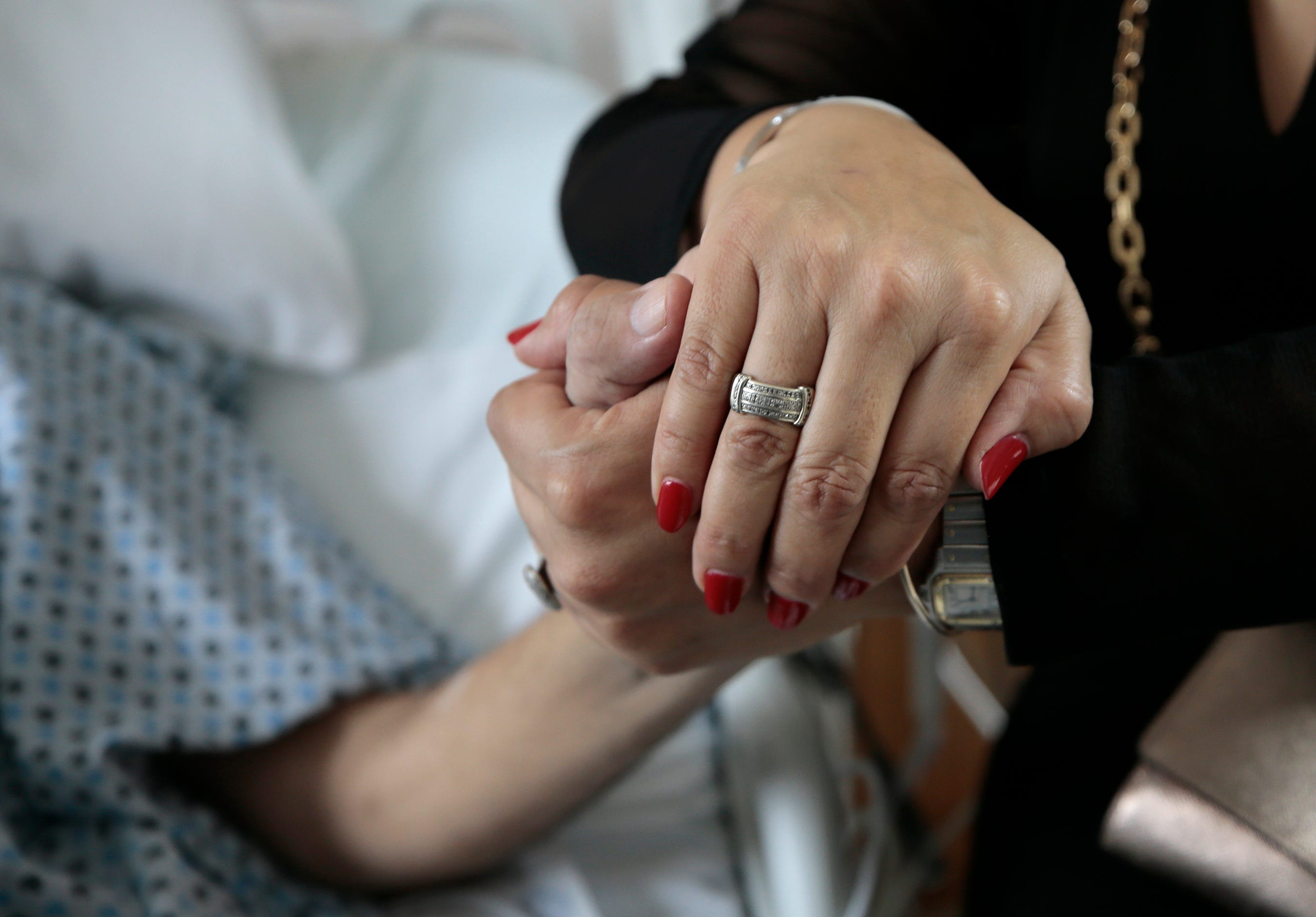 Cristina De Alba holds hands with her brother Mario de Alba, who was shot in the back at the Walmart in El Paso on August, 3, 2019. He is the last of the more than two dozen wounded to be continuously hospitalized after the attack that killed 23 people.