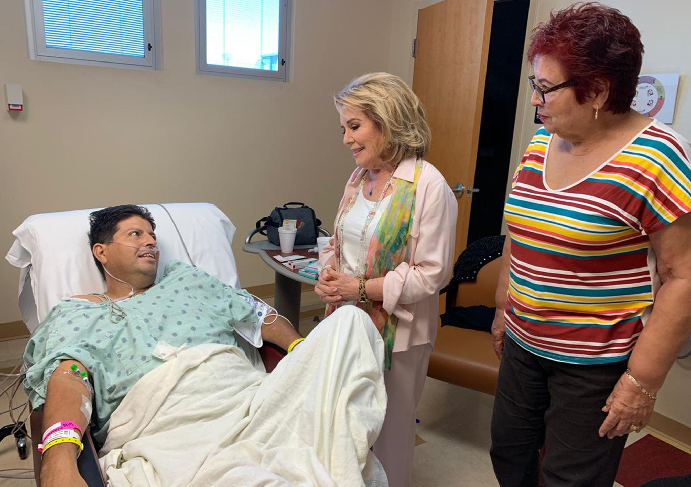 Mario De Alba responds with delight by a visit from his favorite singer Vikki Carr, center, in his hospital room at University Medical Center following the Aug. 3 2019, Walmart mass shooting in El Paso. Carr, who was born in El Paso, serenaded De Alba and his mother, Maria de los Angeles Montes.