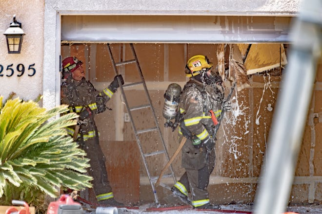 Firefighters pull down wall board in the garage as Tulare Police and Fire investigate a house fire in the 2500 block of Arciero Drive just before noon on Monday, July 27, 2020. Authorities discovered that most of the living space in the house had been converted to growing marijuana. Grow lamps were powered by illegal connections that skipped the electric utility meter. Preliminary assessment revealed the fire started near the electrical panel near and meter before traveling to the attic.
