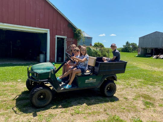 The cousins take the cart once around the farm buildings.