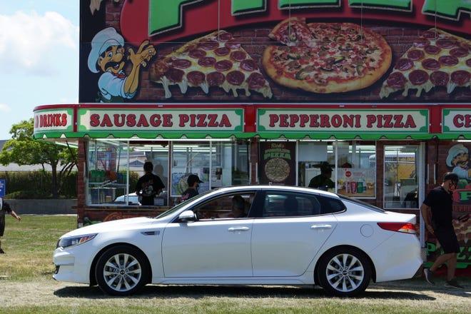 A car waits to pick up pizza at Rick's Pizza.