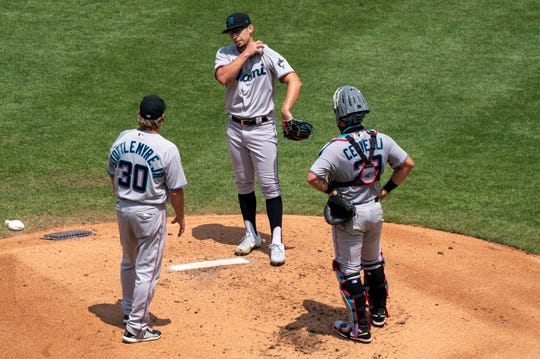 Marlins pitcher Robert Dugger, center, listens to pitching coach Mel Stottlemyre Jr., left, with catcher Francisco Cervelli, right, as they try to social distance during a mound visit vs. the Phillies.