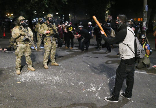 A man upset about federal agents detaining protesters threatens them with a baseball bat and dares them to shoot him during a protest outside the federal courthouse in Portland, Oregon, early on July 27, 2020.
