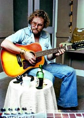 Gordon Lightfoot has a beer handy as he practices in the 1970s.