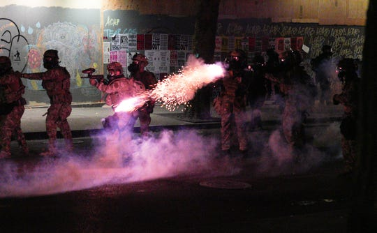 Federal agents form a defensive line and one fires a tear gas gun at advancing protesters outside the federal courthouse in Portland, Oregon, in the early hours of July 27, 2020.