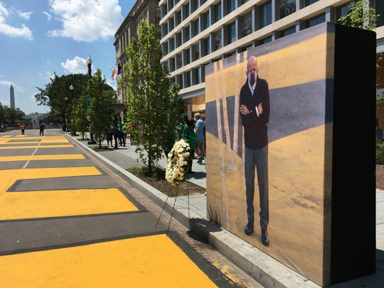 A life-size picture of John Lewis is posted next to a freshly repainted Black Lives Matter street mural near the White House.