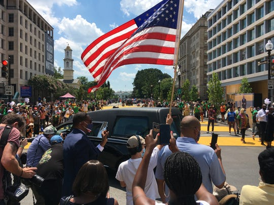 A hearse with the flag-draped casket of Rep. John Lewis, D-Ga., drives on 16th Street, renamed, Black Lives Matter Plaza.