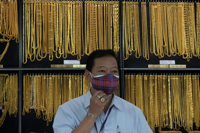 In this April 16, 2020, file photo, a Thai shopkeeper adjusts his face mask at a gold shop in Bangkok, Thailand.