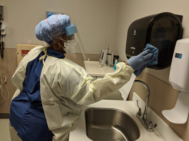 Teameika Magwood, an environmental technician at Candler, wipes down a patient area in the ER.