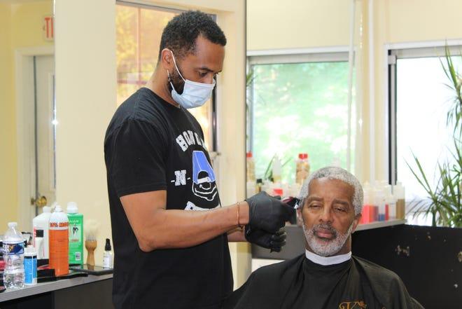 Abbie Watson, owner of GroomKings, 331 W. Loockerman St., cuts a customer's hair.