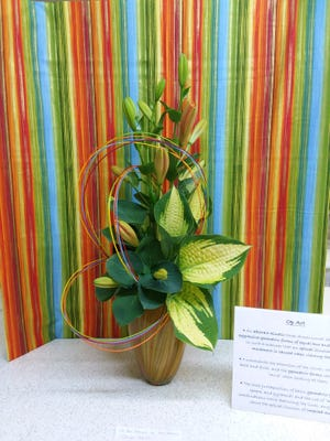 This creative Op Art design titled 'Orange Jubilee' was prepared by Amy Vaughn, a member of the Earth, Wind and Flowers Garden Club. It was displayed all week at the Crawford County Fair flower show so viewers could learn about implied movement.
