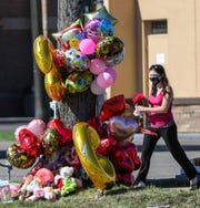 A woman brings items to leave at a memorial that sits at the corner of East 10 mile and Ryan roads in Warren, where a 10-year-old girl was killed when a front end loader fell off a trailer onto her mother's car.