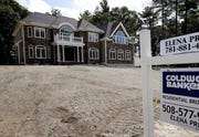In this Sept. 3, 2019 file photo a sign rests in front of a newly constructed home, in Westwood, Mass. U.S. home prices grew more slowly in May, but continued to show resilience in the face of the coronavirus outbreak.