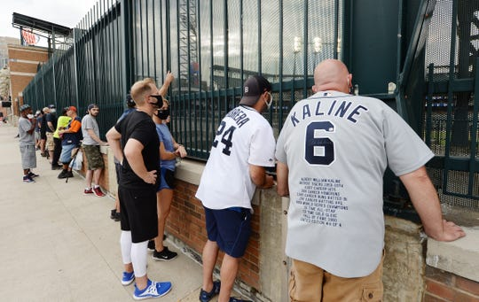 Steve Wade, (Cabrera jersey), 40, of Ferndale and Tom Clifton, 52, (Kaline jersey), of Sterling Heights watch the home opener with other fans outside the centerfield fence at Comerica Park.