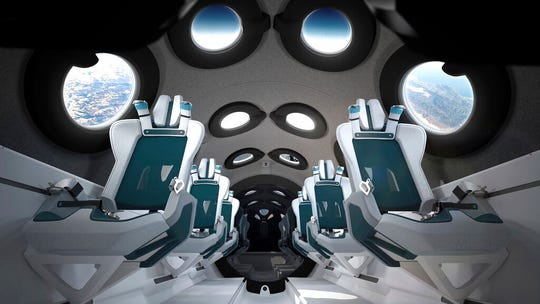 This undated photo released by Virgin Galactic shows the interior of their SpaceshipTwo Cabin during a flight.  There are a dozen windows for viewing, seats capable of being customized to each of six passengers and mood lighting.