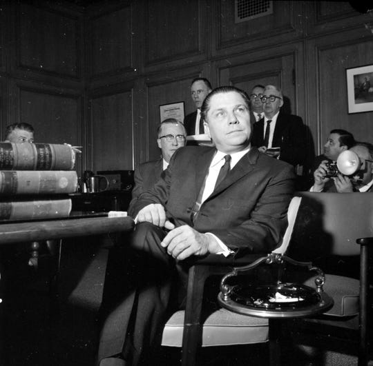 Portrait of Teamster Union leader, Jimmy Hoffa sitting in chair with unidentified men in background during newspaper strike of 1962 in Detroit, Michigan.
