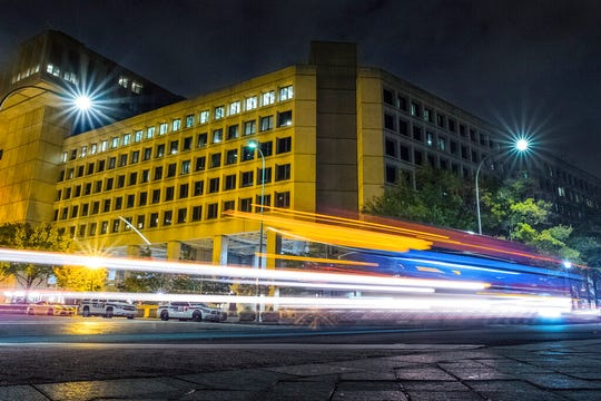 In this Nov. 1, 2017, file photo, traffic along Pennsylvania Avenue in Washington streaks past the Federal Bureau of Investigation headquarters building. Democrats are accusing President Donald Trump of self-dealing as the White House pushes Senate Republicans to include nearly $1.8 billion to rebuild the FBI headquarters in downtown Washington as part of a new coronavirus aid package.