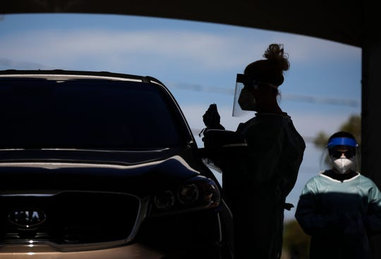 A healthcare workers test patients in their cars at a drive-thru coronavirus testing site in Las Vegas.