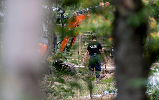Germany police officers search an allotment garden plot in Seelze, near Hannover, Germany, Tuesday July 28, 2020.  Police have begun searching an allotment garden plot, believed to be in connection with the 2007 disappearance of missing British girl Madeleine McCann.