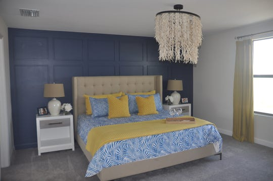 A dark navy wall behind the bed highlights the sleeping area while the bright pops of yellow on the bed give the room a cheery look in the Amalfi model.