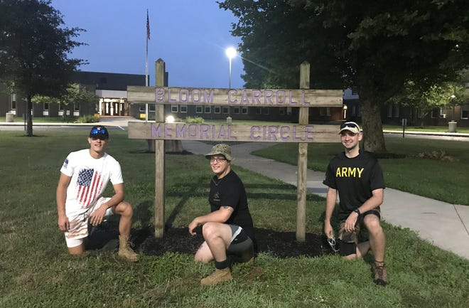 From the left, Josh Hettler, U.S. Army Sgt. Robert Mills and Ben Herdman take a photo at Bloom Carroll High School July 24 as they prepare to hike from Carroll to Dayton as a fundraiser for the Wounded Warrior Project. Hettler and Herdman are rising seniors at Fairfield Christian Academy and plan to join the Army after graduation.