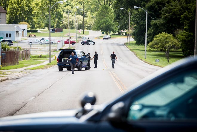 Police on Saturday collect evidence on Dr. Martin Luther King Boulevard, where they said as many as 20 gunshots were exchanged between the occupants of two cars. A 22-year-old passenger in one of the vehicles was wounded by the gunfire.