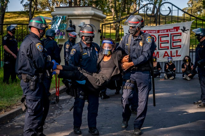 A woman protester is carried away by California Highway Patrol officers outside the gate of California Gov. Gavin Newsom's home in Fair Oaks, Calif., on Monday, July 27, 2020. Demonstrators chained themselves to a fence outside the governor's home, calling for mass inmate releases and an end to immigration transfers because of the coronavirus pandemic, as deaths mounted at a San Francisco Bay Area prison. The CHP cut the chains linking protesters to the bars of the gate at the front of the residence in suburban Sacramento after about two hours, but could not immediately say how many had been arrested.