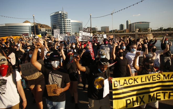Black Lives Matter protesters march over the Mill Avenue bridge during a protest at Tempe Beach Park in Tempe on July 27, 2020.