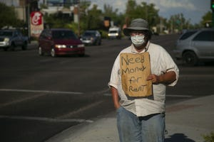 Curtis Hardin of Phoenix stands at Indian School Road and 44th Street in Phoenix asking for money from passing motorists on June 27, 2020. Hardin, who receives disability benefits, says he also had a part-time job as a sign flipper for a jewelry store but lost that job during the COVID-19 pandemic. He is now struggling to pay his rent.