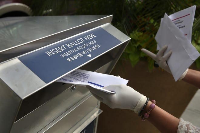FILE - In this July 7, 2020, file photo a woman wearing gloves drops off a mail-in ballot at a drop box in Hackensack, N.J. After months of hearing President Donald Trump denigrate mail-in balloting, Republicans in the critical battleground state now find themselves far behind Democrats in the perennial push to urge their voters to vote remotely. While Democrats have doubled the number of their voters who've asked for a mail ballot compared to 2016, Republicans have only increased by about 20% since the same time. (AP Photo/Seth Wenig, File)