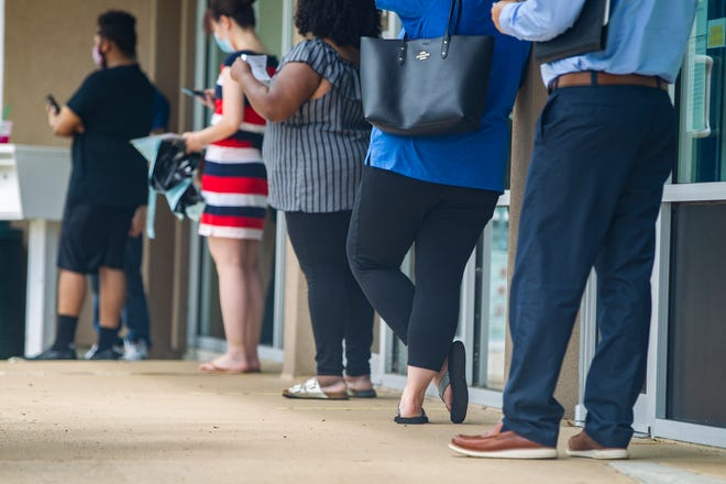 Leon County residents line up outside the Tax Collector's Office located on Monroe Street on Tuesday, July 28, 2020.