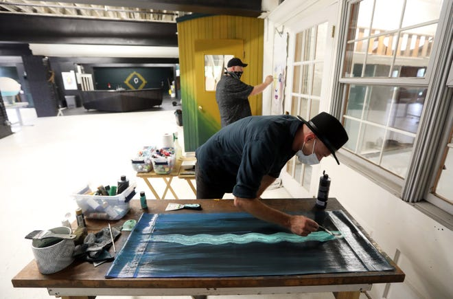 Chris Cassidy, front, and Ike Carr, owners of Carbon Art/Food Collective in Zanesville, paint banners that will hang in downtown Zanesville.
