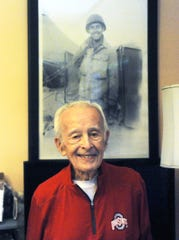 Zanesville resident Joe Pishner poses in front of his Army photo from World War II. Pishner was one of 10 military veterans to be recognized with the Ford Oval of Honor, a part of Red, White and Boom in Columbus. The ceremony was canceled due to COVID-19, but Pishner will be honored at the 2021 event.