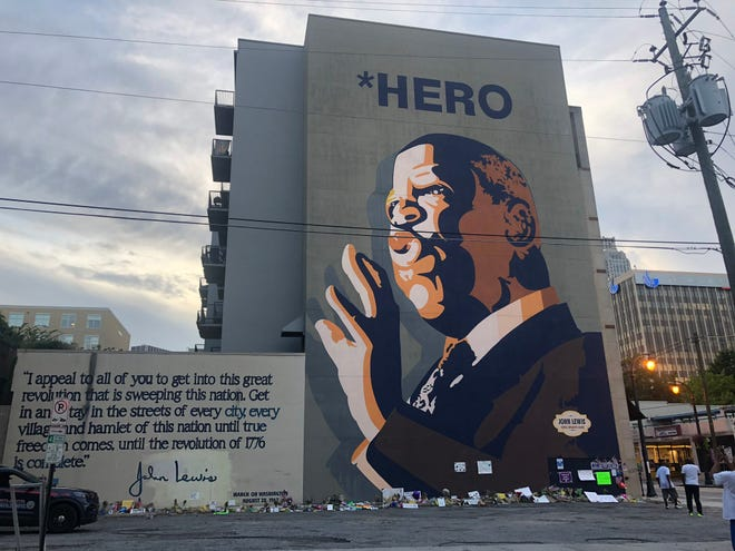 Mourners created a makeshift memorial in front of the John Lewis mural in downtown Atlanta.