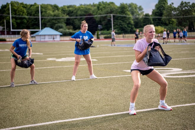 Harper Creek senior volleyball players Emily Martens, Kendyl Ashley and Kylee Crandall run drills with other fall athletes on the Harper Creek High School football field on Tuesday, July 19, 2020 in Battle Creek